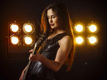 Sexy woman playing electric guitar on stage. Photo of a beautiful young woman playing an electric guitar in front of stage lights Stock Photos
