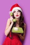 Photo of beautiful young woman with retro phone in santa claus h Stock Image
