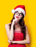 Photo of beautiful young woman in santa claus hat on the wonder. Ful yellow background royalty free stock image