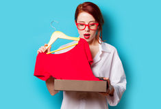 Photo of beautiful young woman with shirt on hanger under box on Royalty Free Stock Photo