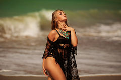 Photo of the beautiful young woman sitting on the beach. Beautiful girl in a black bathing suit on the beach Royalty Free Stock Photo