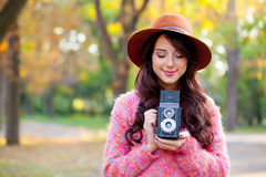 Photo of beautiful young woman standing in the park with retro c Stock Image