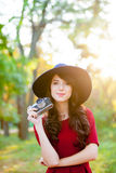 Photo of beautiful young woman standing in the park with retro c Royalty Free Stock Image