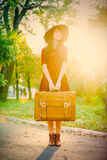 Photo of beautiful young woman with suitcase standing in the par Royalty Free Stock Photo