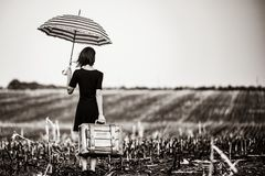 Young woman with suitcase and umbrella. Photo of the beautiful young woman with suitcase and umbrella standing in the middle of the field stock photography