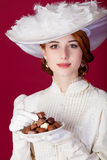 Photo of beautiful young woman in vintage dress with plate full Royalty Free Stock Photos