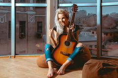 Photo of beauty blonde woman screaming with guitar in her hands Stock Image