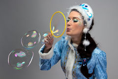 Photo of beauty snow maiden blowing soap bubble Stock Photography