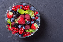Photo of Berries background. Berries in bowl raspberry , blueberry , strawberry , red currant , blackberry Top view with space for text Stock Photos