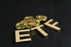 Bitcoin coin with ETF text Put on wooden floor, Concept Entering the Digital Money Fund. royalty free stock image