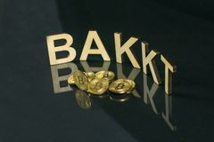 Bitcoin coins in front of bakkt sign made of wood with reflection on the table, Slovenia - December 27th royalty free stock photos