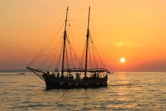 Photo of Black Ship on Body of Water during Sunset Stock Photo