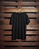 Photo of black tshirt holding on wood background Royalty Free Stock Image