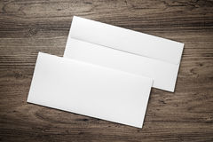 Photo of blank envelopes. Photo of two blank envelopes on a dark wooden table background. Front and back side. Template for branding identity. Top view stock image
