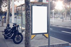 Photo blank lightbox on bus stop in the modern city. Authentic motobike parking close. Horizontal mockup, sunlight Stock Photography