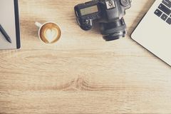 Photo blogger / photographer / it specialist`s typical office space table with laptop, blank screen, coffee cup and electronics. royalty free stock images