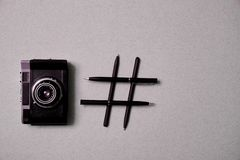 Photo blogging, blog and blogger or social media concept: symbol hashtag and a retro photo camera on a grey background. Flat lay.  stock photography