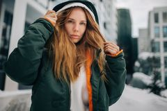 Photo of blond model in hood and in jacket against winter day. Building background Royalty Free Stock Photography