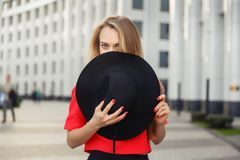 Photo blonde in red jacket covering face with black hat Stock Photos