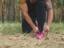 A sporty athlete tying his shoelaces before a training on a natural background. A photo of a body of an athlete tying his shoelaces on a green forest background Stock Photos