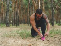 A sporty athlete tying his shoelaces before a training on a natural background. A photo of a bodybuilder on a running tying his shoelaces on a green forest Stock Photography