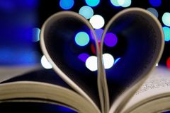 Photo of Bookpages Folded Into Heart Shape With Bokeh Light Background Royalty Free Stock Image
