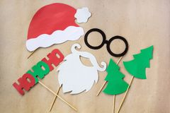 Photo booth colorful props for christmas party - mustache, santa claus, fir tree, glasses, hat. On craft background stock photo