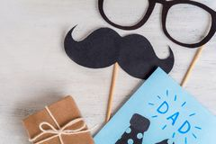 Photo booth mustache and Father Day greeting card. On wooden background royalty free stock image