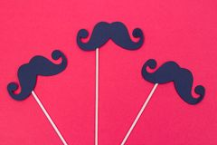 Photo booth props black Mustaches on red background. Photo booth props black Mustaches against red surface royalty free stock photos