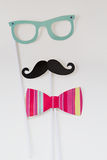 Photo booth props isolated on a white background. Paper photo booth props on sticks isolated on white background includes glasses, mustache and bow tie Royalty Free Stock Photo