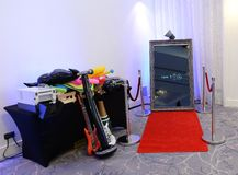 Photo booth set up in a room. Photo booth with guitar, microphone and red carpet set up in room royalty free stock image