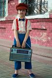 Photo of Boy Holding Radio and Standing Beside of Red House stock photo
