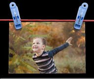 Photo boy on a rope with clothespin on a black background Stock Photos