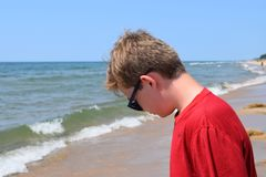 Photo of Boy Wearing Red Shirt and Sunglasses On Seashore royalty free stock photo