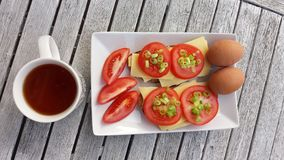 Photo of breakfast: cup of tea eggs and sandwiches with cheese t Stock Images