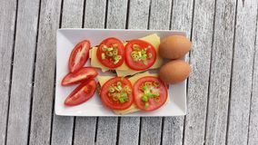 Photo of breakfast: eggs and sandwiches with cheese and tomatoes Stock Photography