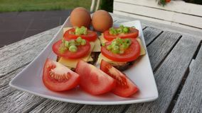 Photo of breakfast: eggs and sandwiches with cheese and tomatoes Royalty Free Stock Images