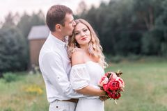 Bride and groom with a bouquet of peonies royalty free stock photos