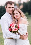 Bride and groom with a bouquet of peonies royalty free stock images
