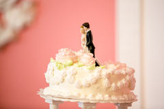 Photo of bride and groom figures on top of wedding cake Stock Photos