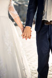Photo of bride and groom holding hands outdoor Stock Photography