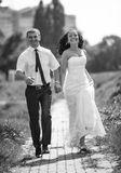 Photo of bride and groom running fast and smiling at park Stock Image