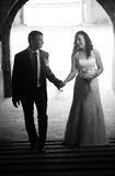 Photo of bride and groom walking under big old arch Royalty Free Stock Photos