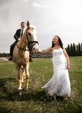 Photo of bride pulling horse by rein with groom riding in saddle Stock Photos