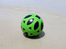 Photo bright rubber ball on the beach. Photo bright beautiful green ball on the beach near the water Stock Photography