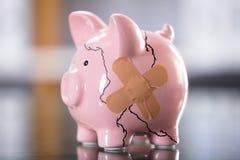 Broken Pink Piggybank. Photo Of Broken Pink Piggybank With Bandage stock image