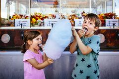 Children eating cotton candy at the carnival. Photo of a brother and sister eating a big cotton candy at an amusement park stock photos