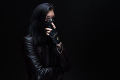 Photo of the brunet with long hair in mask. On black background Stock Image