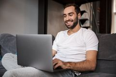 Photo of brunette bachelor using silver laptop while sitting on couch in living room. Photo of brunette bachelor 30s wearing casual t-shirt using silver laptop royalty free stock photo