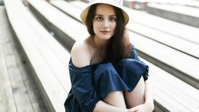 Photo of brunette in hat sitting on bench. Photo of brunette in hat sitting on wooden bench at summer day Stock Photo